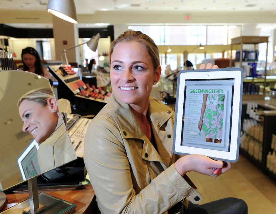 "Laura McKittrick, creator of the ""Greenwich Girl"" lifestyle blog, displays an iPad with her blog at the Saks Fifth Avenue store in Greenwich, Conn., Friday, April 25, 2014.  McKittrick says the makeup counter at Saks is one of her prime locations to gather content and follow fashion trends for her blog. Photo: Bob Luckey / Greenwich Time"