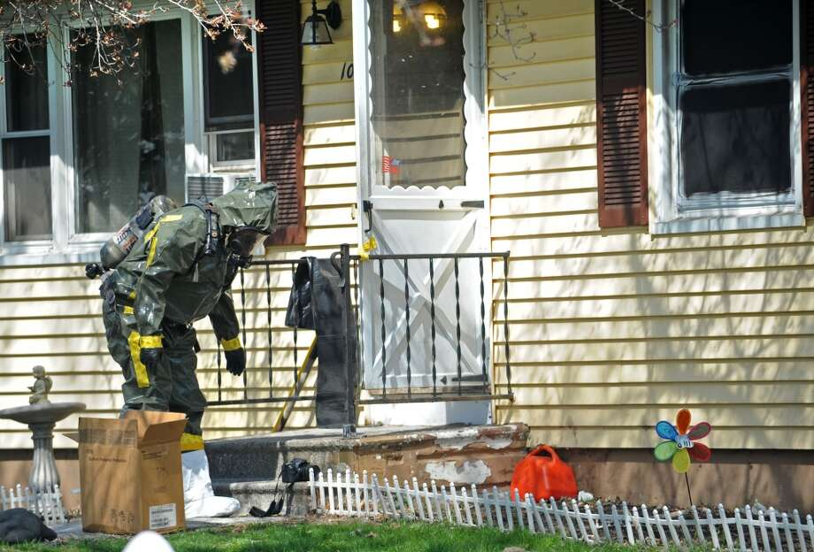 A police officer in a hazmat suit removes items from the scene at 10 Eleanor Road in Seymour, Conn. on Friday, April, 25, 2014. Arthur Gauvin was arrested after his sister Nancy was found being held in the house. Photo: Cathy Zuraw