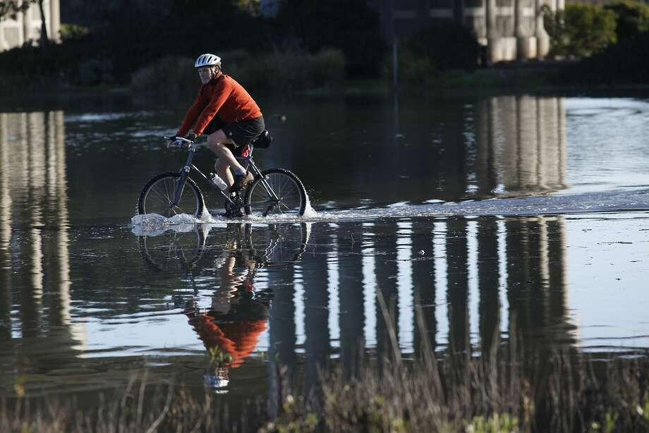 "A cyclist pedals through a flood bike path near the  the Manzanita Park And Ride after a record high tide known as a ""king tide"" hit the San Francisco bay on Wednesday Dec. 12, 2012 in Mill Valley, Calif. Photo: Mike Kepka, The Chronicle"