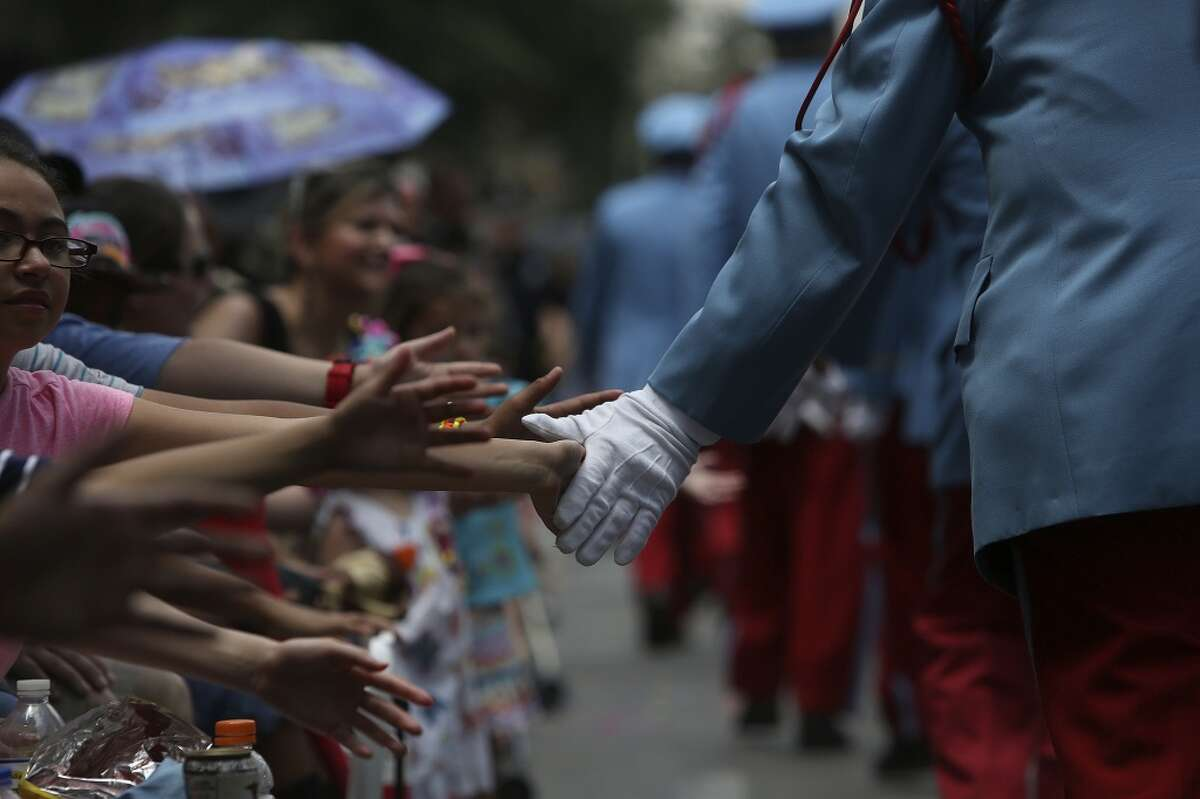 Members of the Texas Cavaliers greet spectators as they walk down Commerce Street during the Battle of Flowers Parade in San Antonio on Friday, April 25, 2014.
