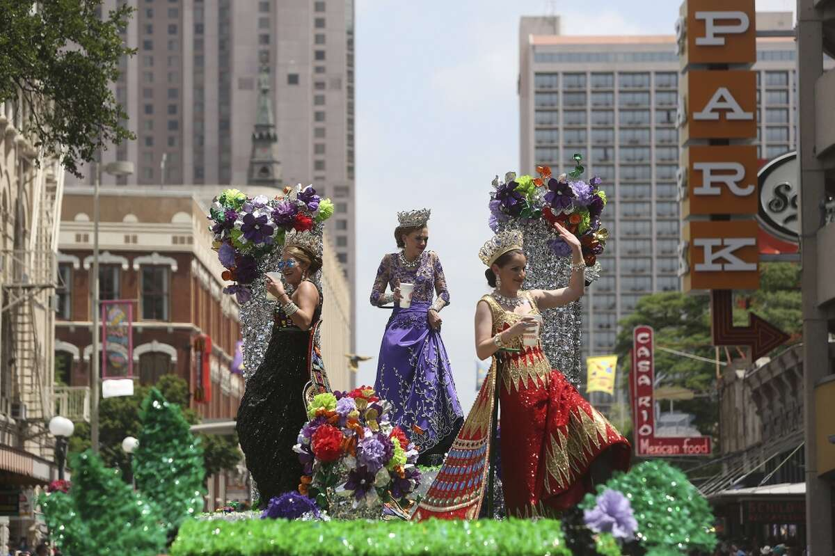 Leslie Asha Ticku, Duchess of the Spirit of Eternal Ascent, from left, Avery Melissa Vaughan, Duchess of the Mystique of Nature, and Mary South Cavender, Duchess of Rare Treasured Discoveries, wave from atop their float during the Battle of Flowers Parade in San Antonio on Friday, April 25, 2014.