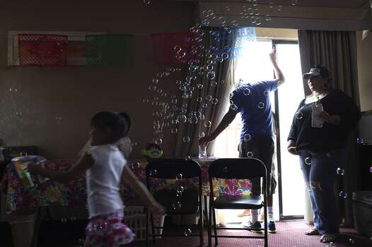 Cathy Villarreal, right, watches as Elena Angel, 4, runs through bubbles in their room at the Travelodge hotel overlooking the parade route on Broadway during the Battle of Flowers Parade in San Antonio on Friday, April 25, 2014. Photo: Lisa Krantz, San Antonio Express-News