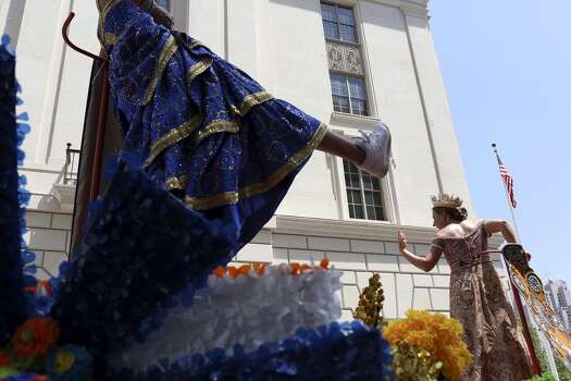 Ina Scott Browning, left, Duchess of the Treasures of Palo Duro, shows her shoes while Katherine Burgwin Fitzsimons, Duchess of Elegant Adornments, right, waves during the Battle of Flowers Parade in San Antonio on Friday, April 25, 2014. Photo: Lisa Krantz, San Antonio Express-News