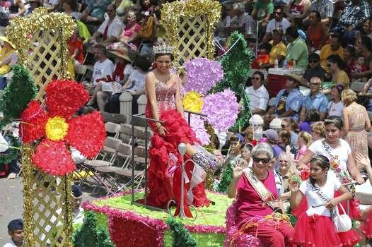 Reina de la Feria de las Flores Marisol Garza (left) shows her boots Friday April 25, 2014 during the Battle of Flowers Parade. Photo: Edward A. Ornelas, San Antonio Express-News