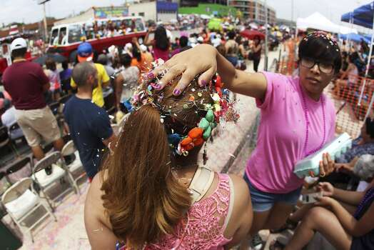 Stephanie Figueroa (right) plops confetti on the head of Isabel Figueroa, her mother-in-law, while watching the 2014 Battle of Flowers parade on Friday, Apr. 25, 2014. (Kin Man Hui/San Antonio Express-News) Photo: Kin Man Hui, San Antonio Express-News