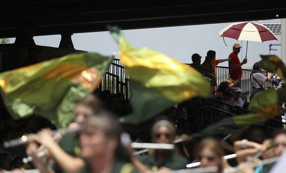 Parade watchers take respite from the heat under umbrellas at the 2014 Battle of Flowers parade on Friday, Apr. 25, 2014. (Kin Man Hui/San Antonio Express-News) Photo: Kin Man Hui, San Antonio Express-News
