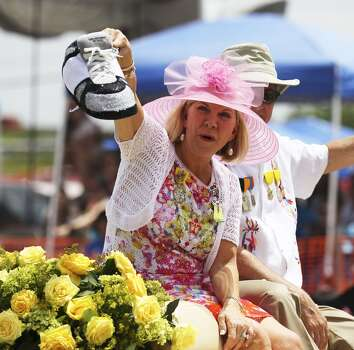 President of the Battle of Flowers Association Anne Mortimer Ballantyne devises a unique way to show off her shoes during the 2014 Battle of Flowers parade on Friday, Apr. 25, 2014. (Kin Man Hui/San Antonio Express-News) Photo: Kin Man Hui, San Antonio Express-News