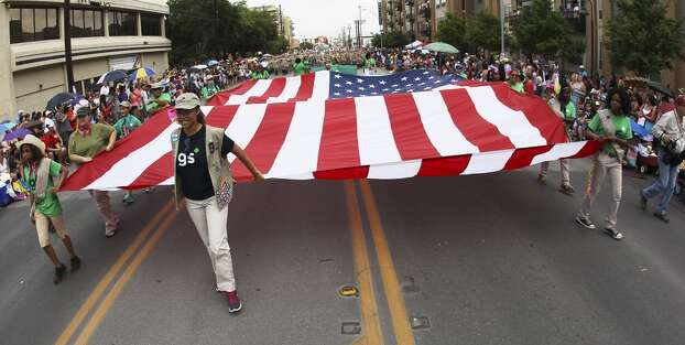 Members of the Girl Scouts of America carry the U.S. Flag at the 2014 Battle of Flowers parade on Friday, Apr. 25, 2014. (Kin Man Hui/San Antonio Express-News) Photo: Kin Man Hui, San Antonio Express-News