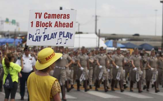 A member of the Battle of Flowers Association holds a sign to cue the bands to play as they approach television cameras at the 2014 Battle of Flowers parade on Friday, Apr. 25, 2014. (Kin Man Hui/San Antonio Express-News) Photo: Kin Man Hui, San Antonio Express-News