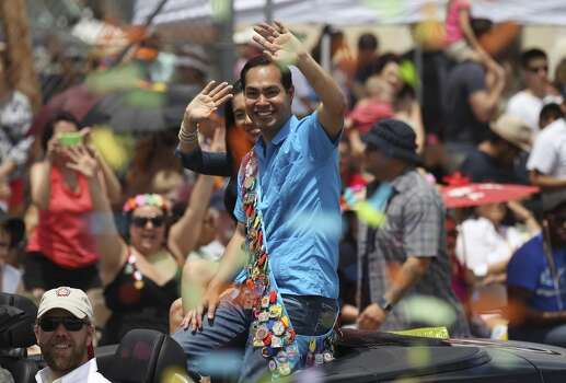 Mayor Julian Castro and his wife, Erica, wave to crowds at the 2014 Battle of Flowers parade on Friday, Apr. 25, 2014. (Kin Man Hui/San Antonio Express-News) Photo: Kin Man Hui, San Antonio Express-News