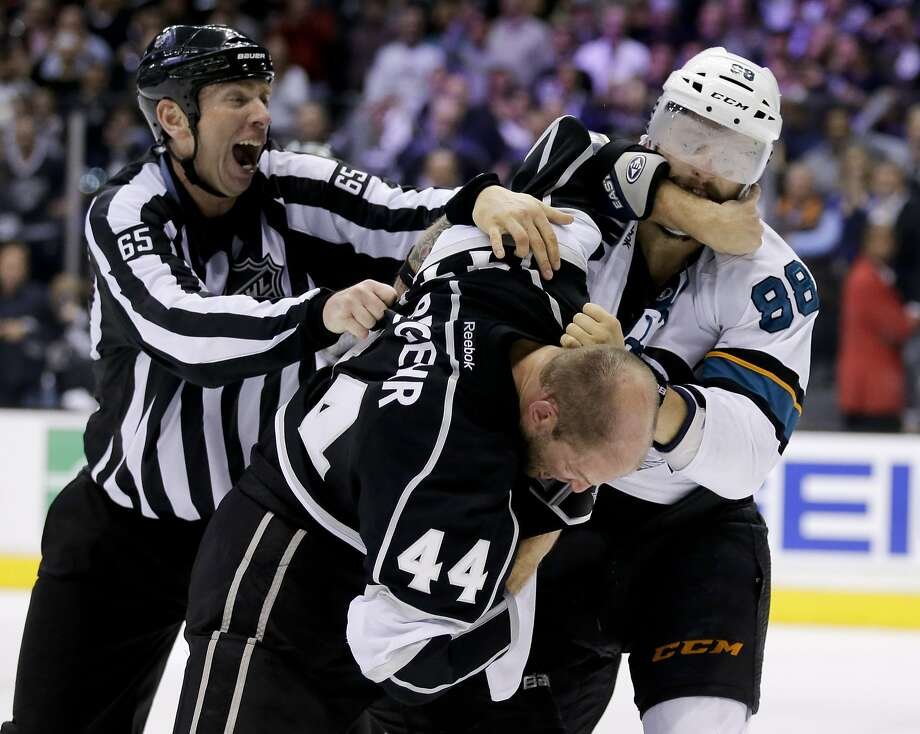 Robyn Regehr (44) and the Sharks' Brent Burns get physical in the third period Thursday. Photo: Chris Carlson, Associated Press