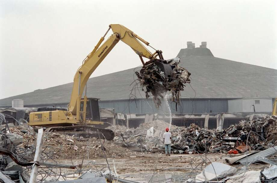Workers with D.H. Griffin of Texas remove the remains of the west wing of the Reliant Astrohall in the shadow of the Astrodome and Reliant Stadium in April 2002. Photo: Karl Stolleis, Houston Chronicle