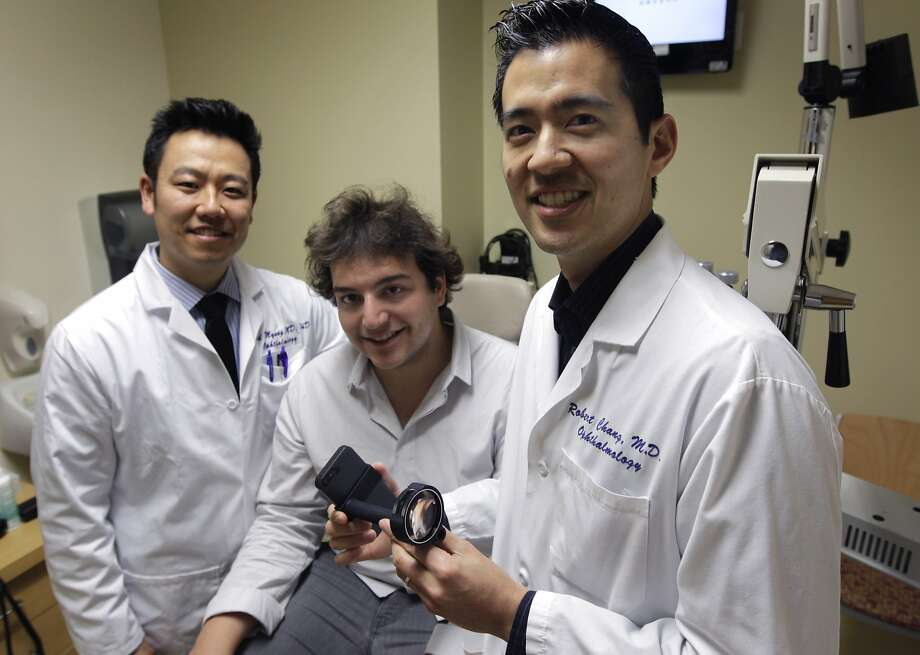 Dr. David Myung (left), Alexandre Jais and Dr. Robert Chang test the EyeGo retina examination adapter, below, a device used with an iPhone that allows physicians to take pictures of the front and back of the eye. Photo: Paul Chinn, The Chronicle