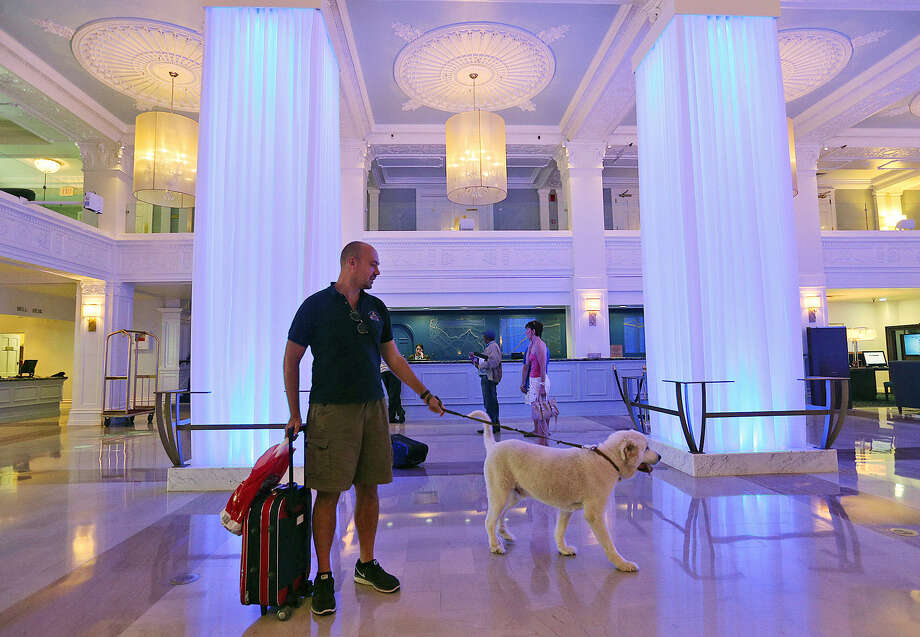 Doug Burgess, 37, waits with his 7-year-old Great Pyrenees, Atticus, in the lobby of the Sheraton Gunter Hotel on Thursday. Burgess, who's from Austin, was in San Antonio for Fiesta. The 104-year-old hotel unveiled a multimillion-dollar renovation last week that includes columns covered in white sheets and lighting that changes colors. Photo: Photos By Jerry Lara / San Antonio Express-News / © 2014 San Antonio Express-News