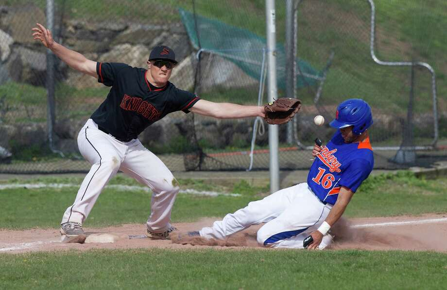 Danbury's Heriberto Rodriguez is safe at third base as Stamford's Jack Rakoczy reaches for the ball during Friday's baseball game at Stamford High School on April 25, 2014. Photo: Lindsay Perry / Stamford Advocate