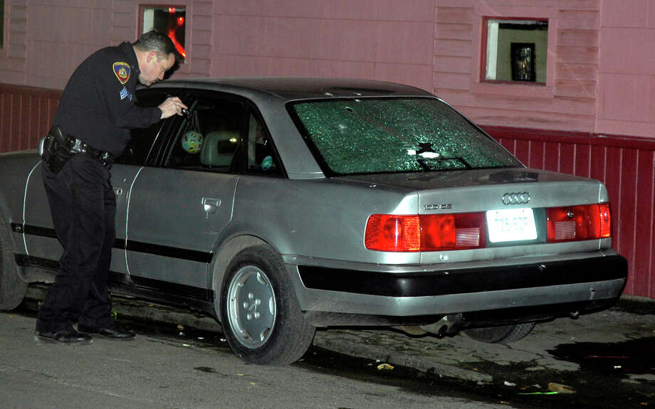 Stamford police Sgt. Richard Phalen looks at a shot up car, parked in front of a barber shop on Pacific Street in Stamford, Conn. where a shooting occurred in 2005. Photo: File Photo / Stamford Advocate file photo