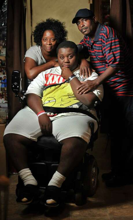 In this photo taken on Monday, March 17, 2014, Audrey and Joseph Stewart pose their son Aubrey, 18, at their home in Jacksonville, Fla. Aubrey is paralyzed and confined to a wheelchair after he was injured by a falling limb across the street from their home when he was 15. (AP Photo/The Florida Times-Union, Will Dickey) Photo: Will Dickey, MBI / Florida Times-Union