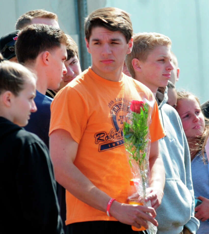 An unidentified student holds flowers at an impromptu memorial for 16-year-old stabbing victim Maren Sanchez outside Jonathan Law High School in Milford, Conn., Friday, April 25, 2014. Sanchez was stabbed to death earlier in the day during an altercation inside the school. A teenage boy is in custody, and police are investigating whether she was stabbed because she declined to be his date at the junior prom. (AP Photo/The New Haven Register, Peter Hvizdak) MANDATORY CREDIT Photo: Peter Hvizdak, MBO / New Haven Register