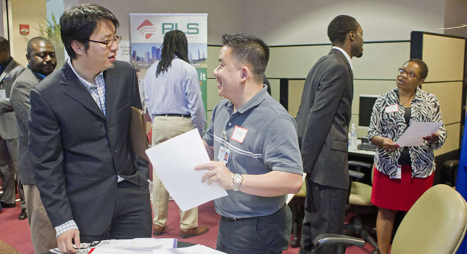 Rick Zhu (left), a Ph.D. candidate in transportation studies at Texas Southern University, discusses the job market with Bach Le, a senior human resources specialist with the city of Houston, during a career fair at the university on Wednesday. Photo: Photos By Johnny Hanson / Houston Chronicle / © 2014  Houston Chronicle