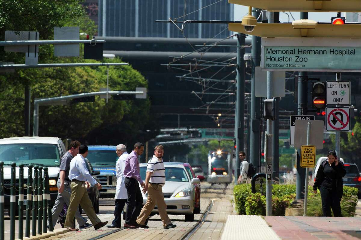 The lunch hour in the Texas Medical Center area finds parades of pedestrians crossing Fannin Street near Memorial Hermann Hospital as noontime traffic ratchets up in addition to the regular light rail operation.