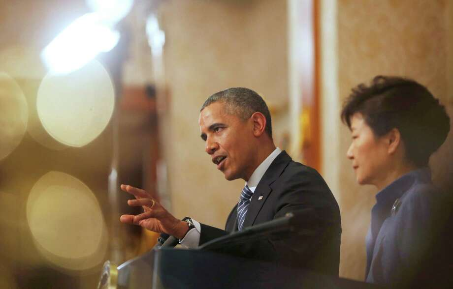 U.S. President Barack Obama, left, answers a reporter's question as South Korean President Park Geun-hye listens during a joint news conference following their meeting at the presidential Blue House in Seoul, Friday, April 25, 2014. (AP Photo/Kim Hong-Ji, Pool) Photo: Kim Hong-ji, POOL / REUTERS POOL