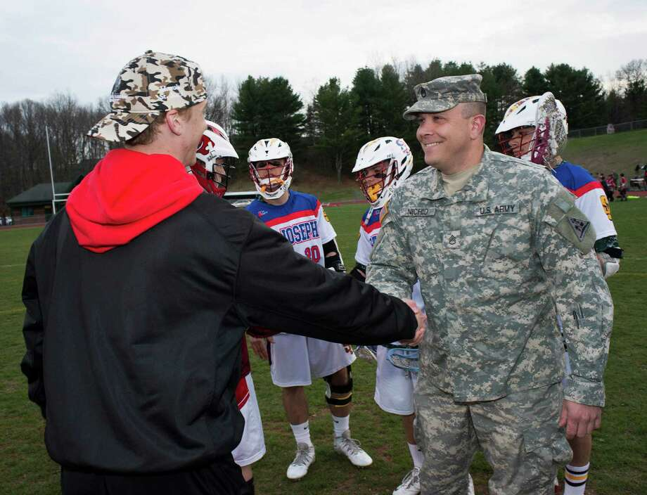 Pete Nichio a member of the United States Army National Guard shakes hands with Masuk high school's Riley Blozzon during a ceremony for the Wounded Warrior Project at the start of a boys lacrosse game between Masuk and St. Joseph high school played at Masuk high school, Monroe, CT on Friday, April, 25th, 2014. Photo: Mark Conrad / Connecticut Post Freelance