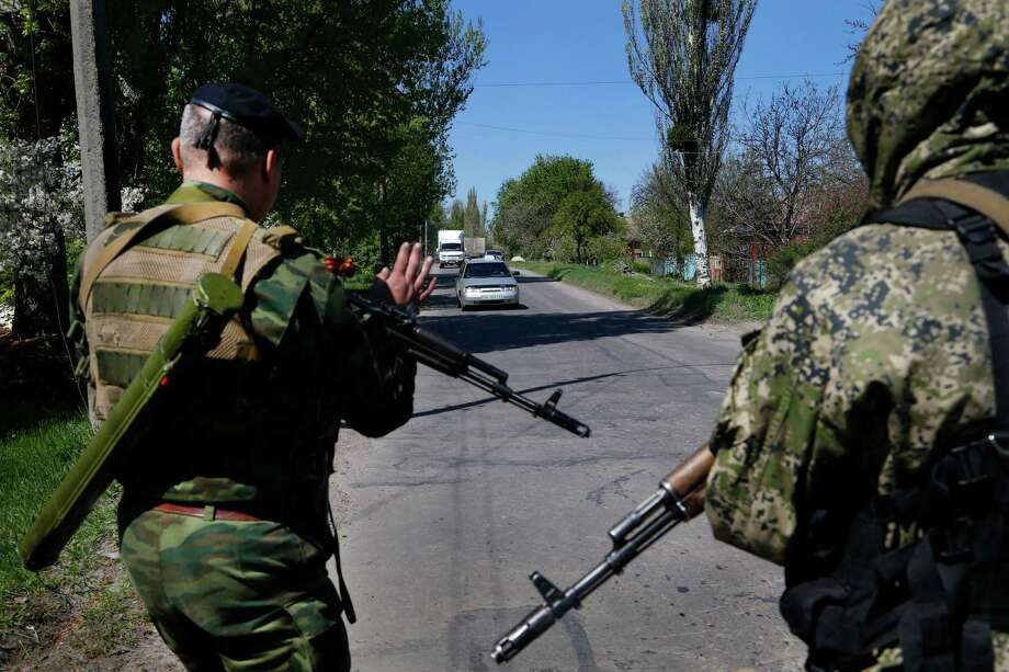 Armed Pro Russian militants signal an approaching car near Slovyansk, eastern Ukraine, Friday, April 25, 2014. Russian Foreign Minister Sergey Lavrov has accused the West of plotting to control Ukraine and said the pro-Russian insurgents in the southeast would lay down their arms only if the Ukrainian government clears out the Maidan protest camp in the capital Kiev. (AP Photo/Sergei Grits) ORG XMIT: XSG115 Photo: Sergei Grits / AP