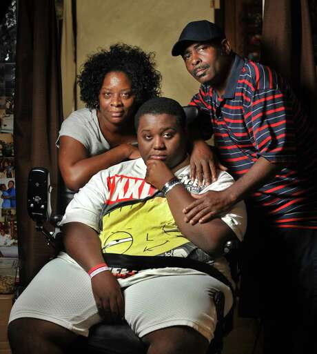 Parents Audrey and Joseph Stewart pose with Aubrey Stewart, 18, at their home in Jacksonville, Fla. Aubrey was injured by a falling limb across the street from their home when he was 15. Photo: Will Dickey / Associated Press / Florida Times-Union