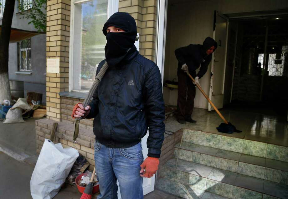 A pro-Russian militant guards a seized police station during unrest Friday in Slovyansk, Ukraine. Photo: Sergei Grits, STF / AP