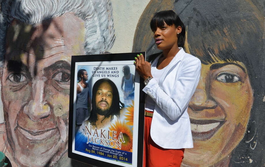 Shackelia Jackson-Thomas holds a poster showing her brother, Nakiea Jackson, who was allegedly slain by a policeman as he cooked in his small shop in Kingston, Jamaica. Photo: David McFadden / Associated Press / AP
