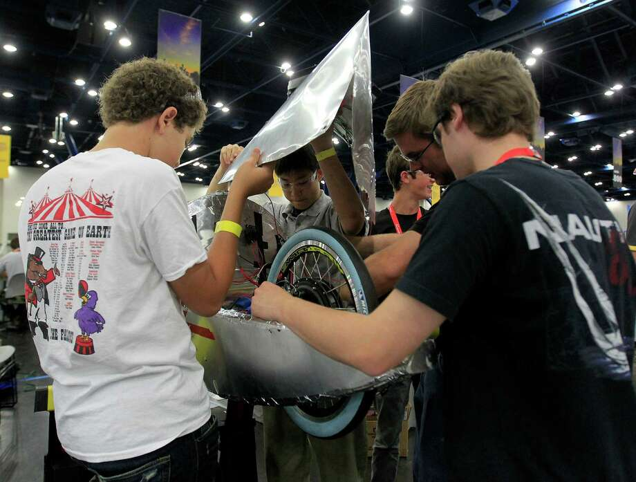 Members of the St. John's School team, of Houston, work on placing the solar panel on their prototype car at Shell's Eco-Marathon Americas competition at the George R. Brown Convention center, Friday, April 25, 2014, in Houston. Photo: Karen Warren, Houston Chronicle / © 2014 Houston Chronicle