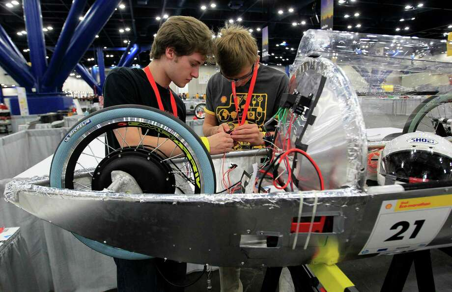 Richard Appel, 16, left, and Jake Peacock, 18, right, of St. John's School in Houston, work on wiring their team's prototype car at Shell's Eco-Marathon Americas competition at the George R. Brown Convention center, Friday, April 25, 2014, in Houston. Photo: Karen Warren, Houston Chronicle / © 2014 Houston Chronicle