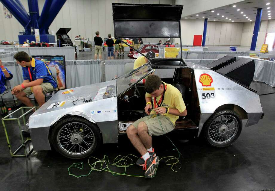 "Marcus Garner, 16, with St. Pauls School in Covington LA, works to wire the turn signals on his team's prototype  ""DeLorean""at Shell's Eco-Marathon Americas competition at the George R. Brown Convention center, Friday, April 25, 2014, in Houston. Photo: Karen Warren, Houston Chronicle / © 2014 Houston Chronicle"