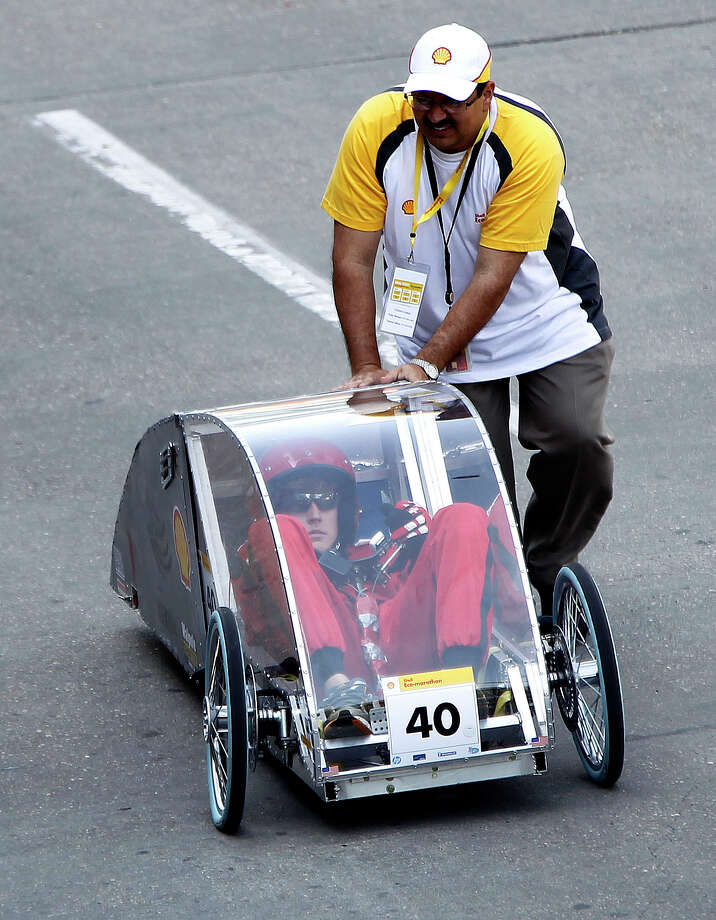 Tanner Stark, 17, of Ruston High School in Ruston, LA, gets a little help back to the paddocks during a test drive in a prototype car at Shell's Eco-Marathon Americas competition at the George R. Brown Convention center, Friday, April 25, 2014, in Houston. Photo: Karen Warren, Houston Chronicle / © 2014 Houston Chronicle