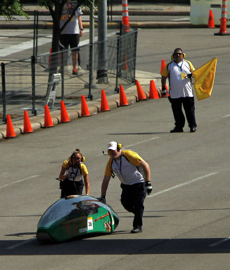 Crew members help push a disabled prototype car back to the start at Shell's Eco-Marathon Americas competition at the George R. Brown Convention center, Friday, April 25, 2014, in Houston. Photo: Karen Warren, Houston Chronicle / © 2014 Houston Chronicle