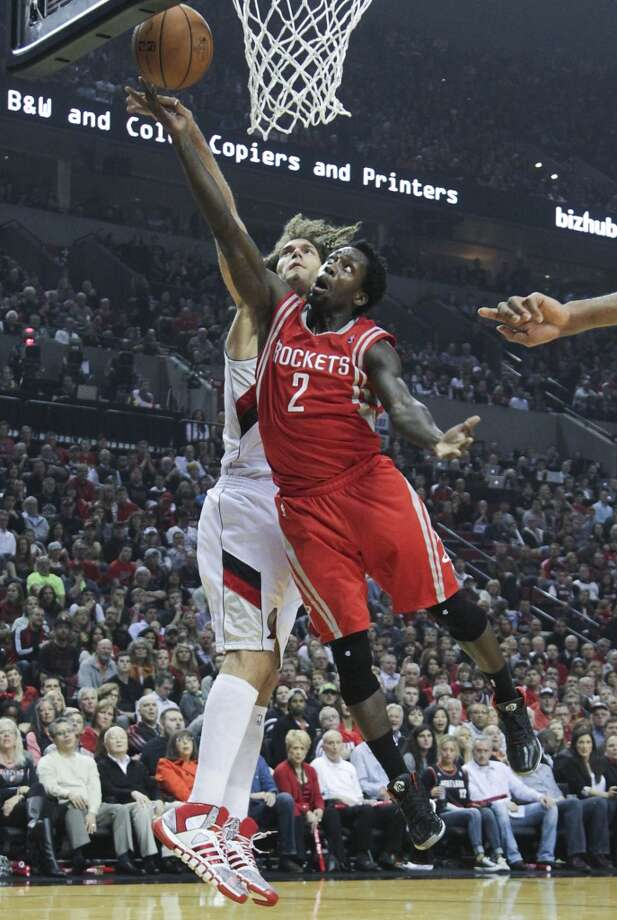 Houston's Patrick Beverley drives to the basket as  Portland's Robin Lopez defends. Photo: James Nielsen, Houston Chronicle