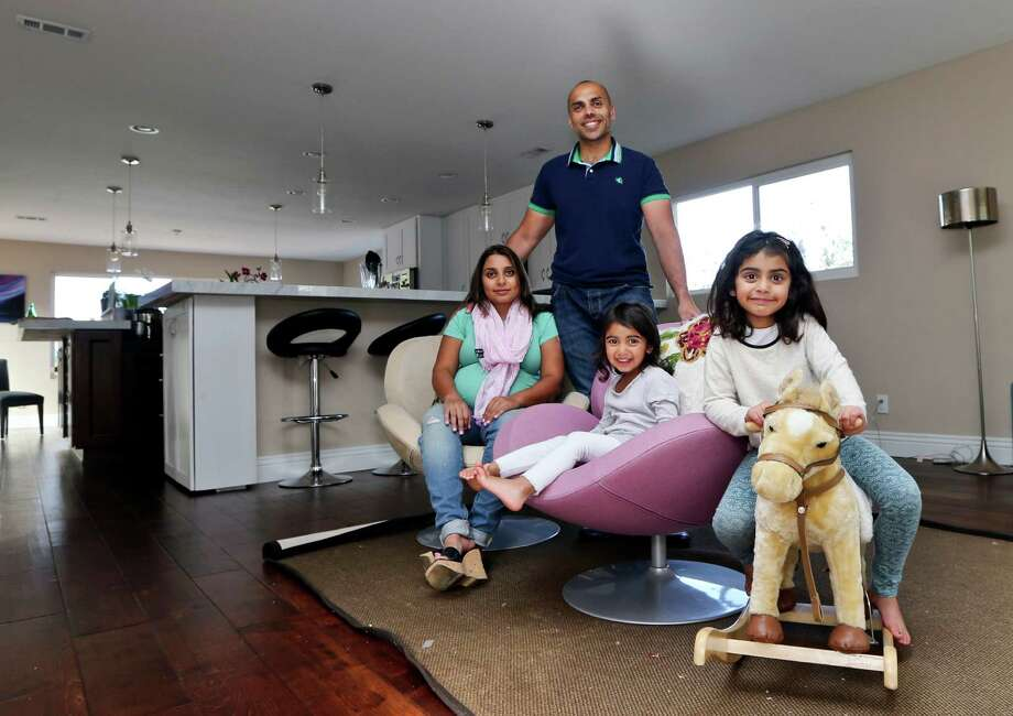 In this April 16, 2014 photo, the Jaswal family, Imran, standing, his wife Aniqa, left, and daughters, Arissa, right, and Jayda, pose for photos in the family room at their home in La Jolla, Calif. The couple bought the four-bedroom house about 10 minutes from the beach in Febrauary. Once Imran's management consulting business began flourishing, the couple felt comfortable enough after years of renting to buy their first home. (AP Photo/Lenny Ignelzi) Photo: Lenny Ignelzi, STF / AP