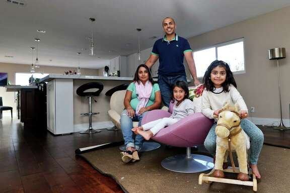 In this April 16, 2014 photo, the Jaswal family, Imran, standing, his wife Aniqa, left, and daughters, Arissa, right, and Jayda, pose for photos in the family room at their home in La Jolla, Calif. The couple bought the four-bedroom house about 10 minutes from the beach in Febrauary. Once Imran's management consulting business began flourishing, the couple felt comfortable enough after years of renting to buy their first home. (AP Photo/Lenny Ignelzi)