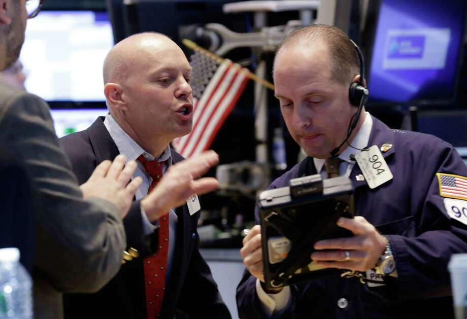 FILE - Traders Daniel Leporin, left, and Michael Urkonis work on the floor of the New York Stock Exchange in this April 23, 2014 file photo. Global stocks tumbled Friday April 25, 2014 after tensions over Ukraine mounted and Standard & Poor's cut Russia's credit rating, warning of capital flight and risks to investment due to the crisis. (AP Photo/Richard Drew, File) Photo: Richard Drew, STF / AP