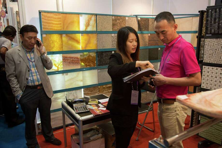 Yan Xiaowei, right, discusses business details this month with a colleague at the Canton Fair, China's main trade show for exporters, in Guangzhou. Photo: THEODORE KAYE, STR / NYTNS