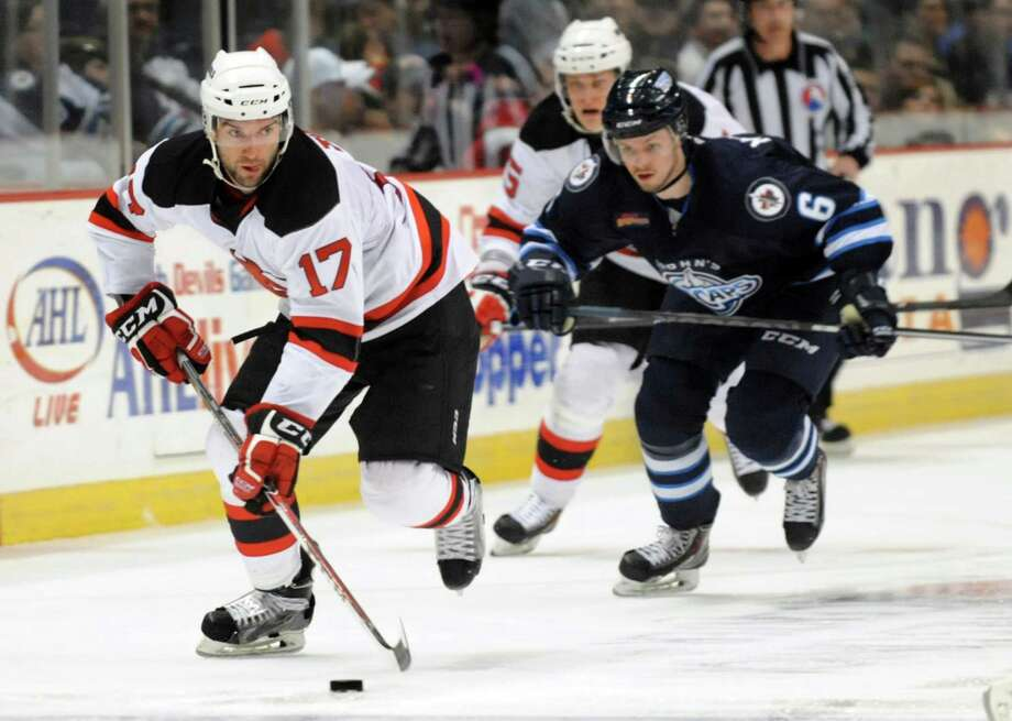 Devils' Scott Timmins, left, guides the puck during their first-round playoff hockey game against the IceCaps on Friday, April 25, 2014, at Times Union Center in Albany, N.Y. (Cindy Schultz / Times Union) Photo: Cindy Schultz / 00026568A