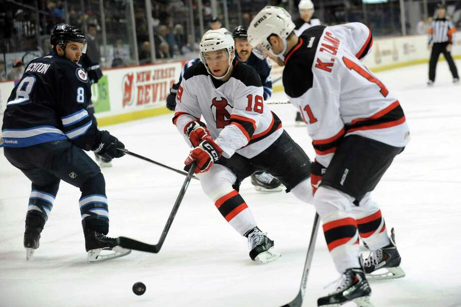 Devils' Stefan Matteau, center, controls the puck during their first-round playoff hockey game against the IceCaps on Friday, April 25, 2014, at Times Union Center in Albany, N.Y. (Cindy Schultz / Times Union) Photo: Cindy Schultz / 00026568A