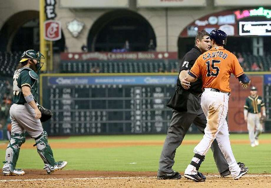 Home plate umpire Jordan Baker walks Astros catcher Jason Castro to first base after he was hit by a pitch in the ninth inning. Photo: Thomas B. Shea, For The Chronicle