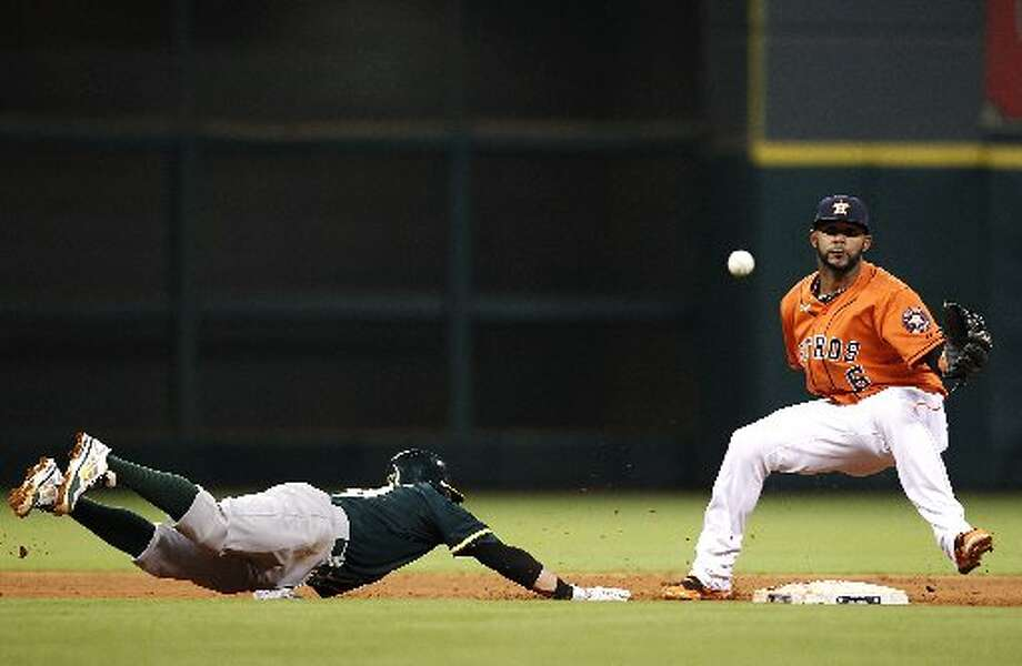Athletics second baseman Eric Sogard (28) dives back after trying to get picked off by Houston Astros manager Bo Porter (16) in the fourth inning on April 25, 2014 at Minute Maid Park in Houston, TX. Sogard advanced to third after Houston Astros shortstop Jonathan Villar (6) couldn't catch the throw. Photo: Thomas B. Shea, For The Chronicle