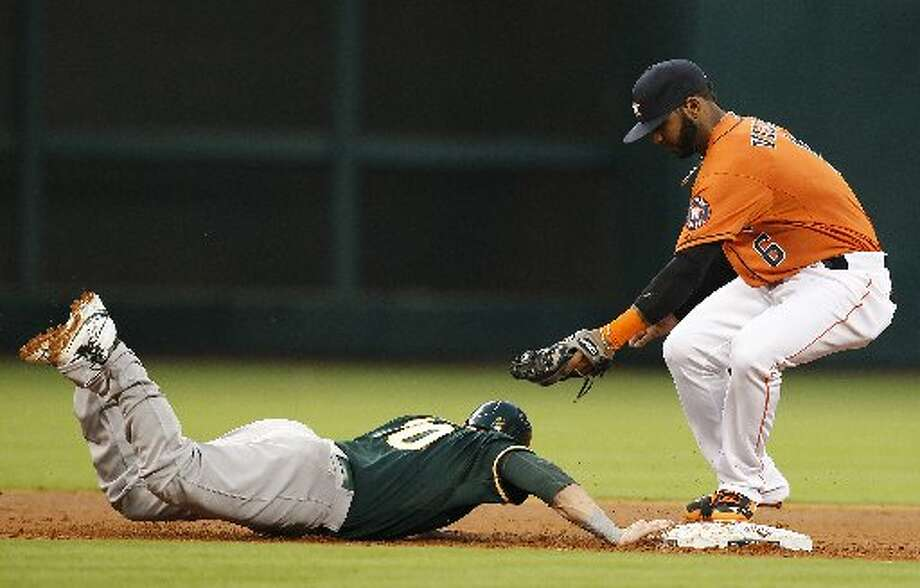 Athletics first baseman Daric Barton (10) dives safely back to second base while Houston Astros shortstop Jonathan Villar (6) is late with the tag in the second inning. Photo: Thomas B. Shea, For The Chronicle