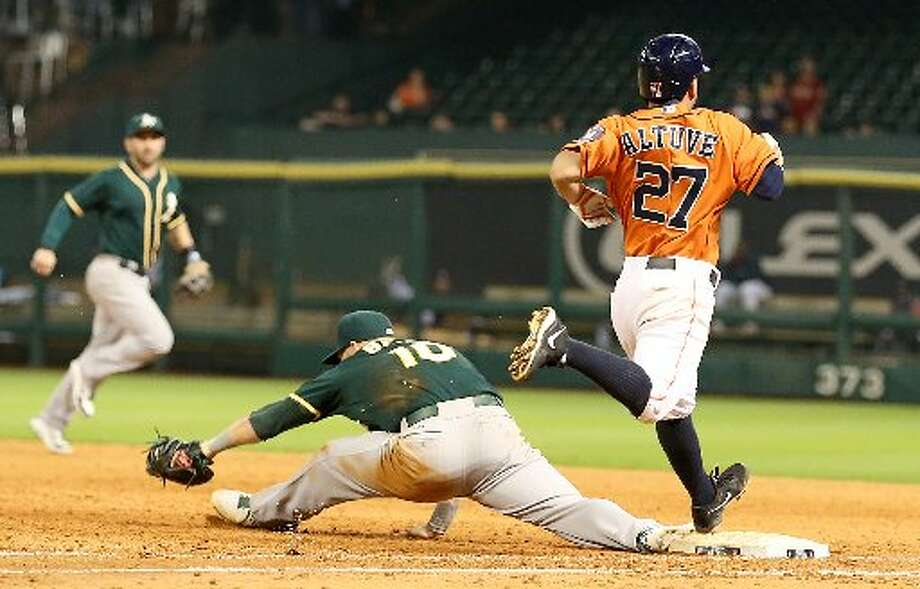 Astros second baseman Jose Altuve (27) is thrown out at first base while Oakland Athletics first baseman Daric Barton (10) stretches in the bottom of the eighth inning. Photo: Thomas B. Shea, For The Chronicle