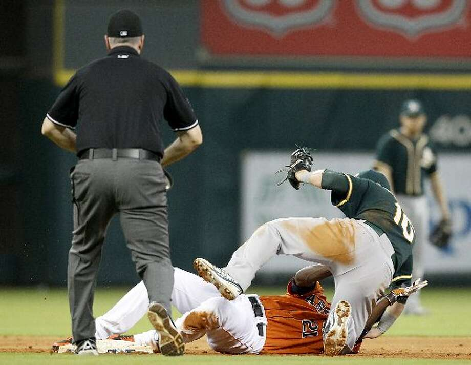 Astros center fielder Dexter Fowler (21) slides safely under Oakland Athletics first baseman Daric Barton (10) in the fourth inning. Photo: Thomas B. Shea, For The Chronicle