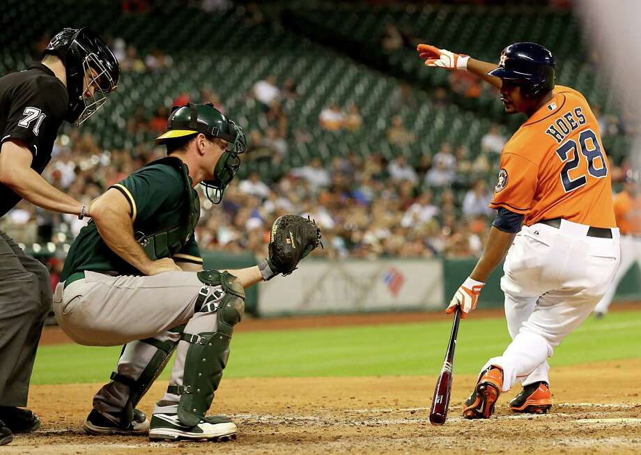Just as he feared, Astros pinch hitter L.J. Hoes, right, takes a glance back at the catcher's mitt to confirm his swinging strikeout during the seventh inning of a 12-5 loss to the Athletics on Friday night. Photo: Thomas B. Shea, Freelance / © 2014 Thomas B. Shea