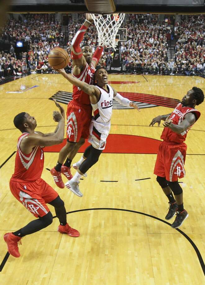 Portland Trail Blazers guard Damian Lillard drives between Houston Rockets center Dwight Howard, forward Terrence Jones and guard Patrick Beverley. Photo: James Nielsen, Houston Chronicle