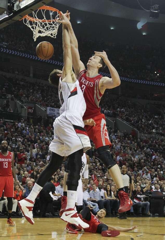 Rockets center Omer Asik dunks over Portland  center Joel Freeland. Photo: James Nielsen, Houston Chronicle